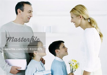 Man with boy and girl facing woman with gifts and flowers Stock Photo - Premium Royalty-Free, Image code: 632-01151571