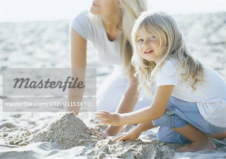 Girl and mother playing in sand Stock Photo - Premium Royalty-Free, Image code: 632-01153630