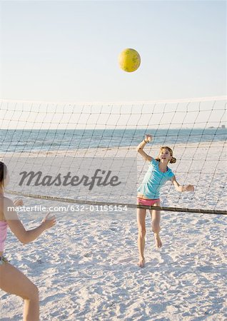 Two girls playing beach volleyball