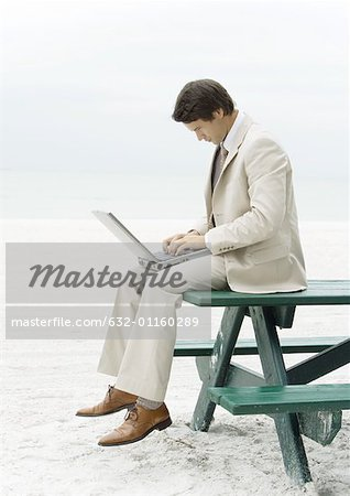 Businessman sitting on edge of picnic table at beach, using laptop Stock Photo - Premium Royalty-Free, Image code: 632-01160289