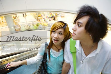Teenage couple riding escalator in mall Stock Photo - Premium Royalty-Free, Image code: 632-01271949