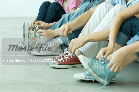 Four teen friends tying laces, all wearing canvas shoes Stock Photo - Premium Royalty-Free, Image code: 632-01379229