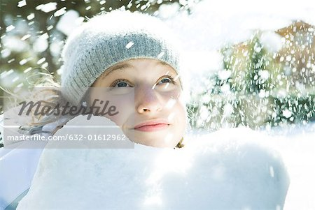 Teenage girl looking up at snow, smiling, portrait Stock Photo - Premium Royalty-Free, Image code: 632-01612962