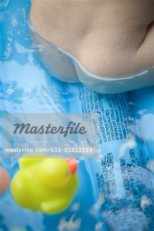 Naked baby sitting in wading pool, cropped view of buttocks Stock Photo - Premium Royalty-Free, Image code: 632-01613289