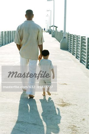Father and son walking together, holding hands, rear view Stock Photo - Premium Royalty-Free, Image code: 632-01827727