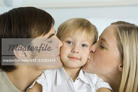 Parents kissing little boy's cheeks, boy smiling at camera Stock Photo - Premium Royalty-Free, Image code: 632-02282919