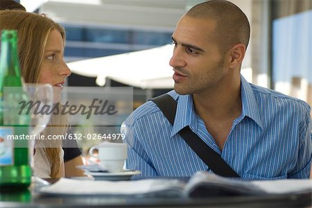 Man and woman sitting in outdoor cafe, having serious conversation Stock Photo - Premium Royalty-Free, Image code: 632-02644979