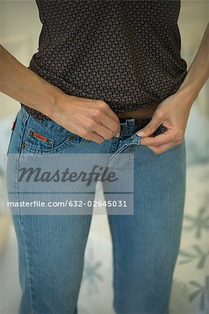 Woman fastening tight jeans, cropped view Stock Photo - Premium Royalty-Free, Image code: 632-02645031