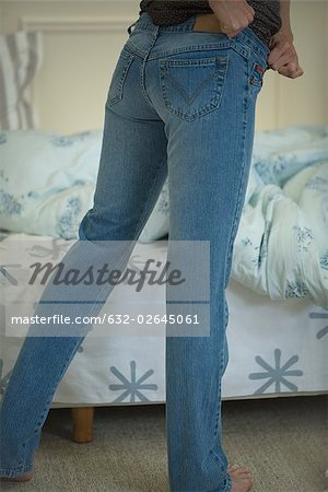 Woman putting on snug-fitting jeans, cropped view Stock Photo - Premium Royalty-Free, Image code: 632-02645061
