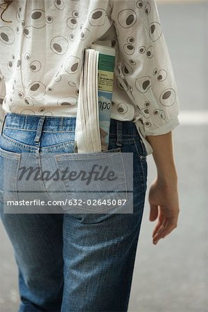 Woman with newspaper rolled up in back pocket of jeans, cropped view Stock Photo - Premium Royalty-Free, Image code: 632-02645087
