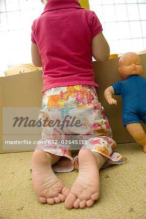 Little girl kneeling before box of toys, rear view Stock Photo - Premium Royalty-Free, Image code: 632-02645119