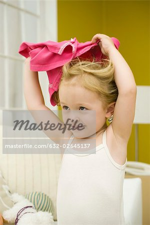 Little girl holding shirt over her head Stock Photo - Premium Royalty-Free, Image code: 632-02645137