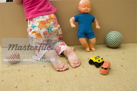 Little girl kneeling on floor with toys, rear view, cropped Stock Photo - Premium Royalty-Free, Image code: 632-02645139