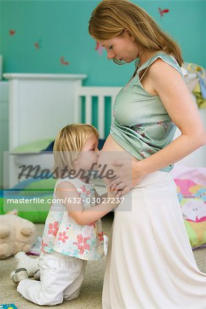 Little girl kissing mother's pregnant belly Stock Photo - Premium Royalty-Free, Image code: 632-03027237
