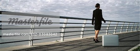 Briefcase set on ground near waterfront railing, businesswoman walking away Stock Photo - Premium Royalty-Free, Image code: 632-03083042