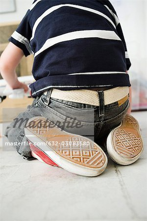 Little boy kneeling on floor, rear view Stock Photo - Premium Royalty-Free, Image code: 632-03083580