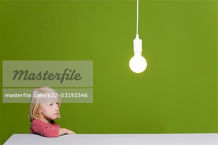 Little girl biting lip looking with concern up at illuminated light bulb suspended overhead Stock Photo - Premium Royalty-Free, Image code: 632-03193346