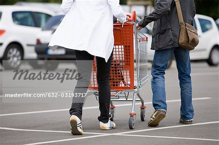 Shoppers pushing shopping cart in parking lot Stock Photo - Premium Royalty-Free, Image code: 632-03193717