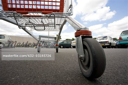 Shopping cart in parking lot, surface level view Stock Photo - Premium Royalty-Free, Image code: 632-03193726