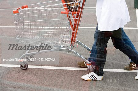 Empty shopping cart being pushed across parking lot Stock Photo - Premium Royalty-Free, Image code: 632-03193742
