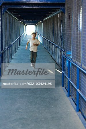 Preteen boy running down corridor, front view Stock Photo - Premium Royalty-Free, Image code: 632-03424195