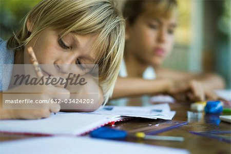 Junior high student resting head on arm while writing assignment Stock Photo - Premium Royalty-Free, Image code: 632-03424202