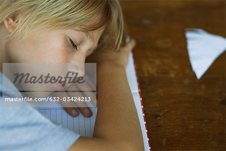 Preteen boy sleeping, resting head on arms laid across notebook Stock Photo - Premium Royalty-Free, Image code: 632-03424213