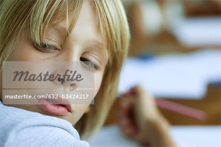 Boy looking over shoulder, distracted from work Stock Photo - Premium Royalty-Free, Image code: 632-03424217