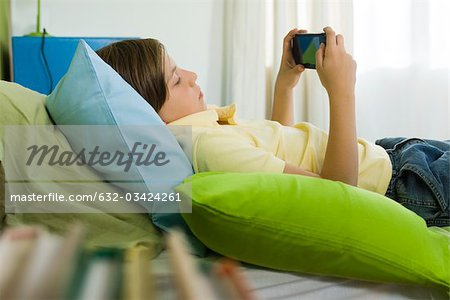 Preteen boy playing handheld video game Stock Photo - Premium Royalty-Free, Image code: 632-03424261