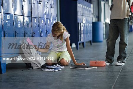 Junior high student picking up dropped school supplies, boy standing by watching Stock Photo - Premium Royalty-Free, Image code: 632-03424528