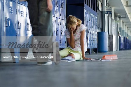 Junior high student sitting on floor crying, boy standing by watching Stock Photo - Premium Royalty-Free, Image code: 632-03424530