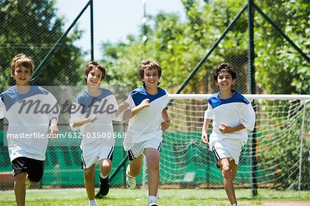 Boys running on soccer field Stock Photo - Premium Royalty-Free, Image code: 632-03500668
