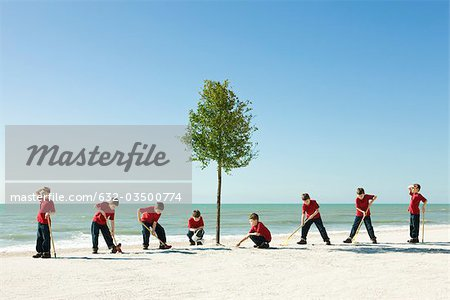 Boy caring for tree planted on sandy beach Stock Photo - Premium Royalty-Free, Image code: 632-03500774