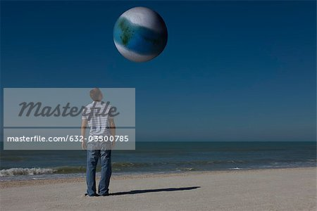 Man on beach looking up at alien world orbiting overhead Stock Photo - Premium Royalty-Free, Image code: 632-03500785
