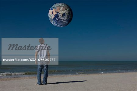 Man on beach looking up at planet earth orbiting overhead Stock Photo - Premium Royalty-Free, Image code: 632-03500787