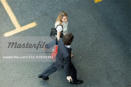 Couple walking together across parking lot, woman carrying shopping bags Stock Photo - Premium Royalty-Free, Image code: 632-03500883
