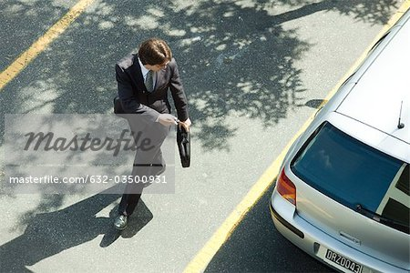 Man locking car doors using key remote as he walks away Stock Photo - Premium Royalty-Free, Image code: 632-03500931