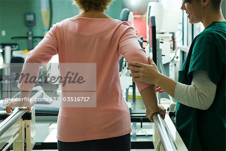 Patient undergoing rehabilitation walking exercises with assistance from physical therapist Stock Photo - Premium Royalty-Free, Image code: 632-03516717
