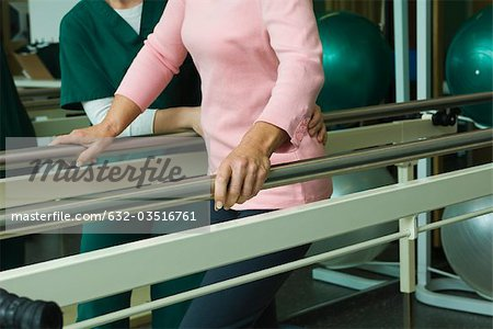 Patient undergoing post-surgery rehabilitation exercises to regain ability to walk Stock Photo - Premium Royalty-Free, Image code: 632-03516761