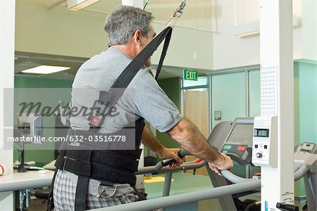 Man exercising on treadmill with assistance of rehabilitation harness supporting body weight Stock Photo - Premium Royalty-Free, Image code: 632-03516778