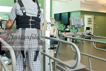 Man exercising on treadmill with assistance of rehabilitation harness supporting body weight Stock Photo - Premium Royalty-Free, Image code: 632-03516786