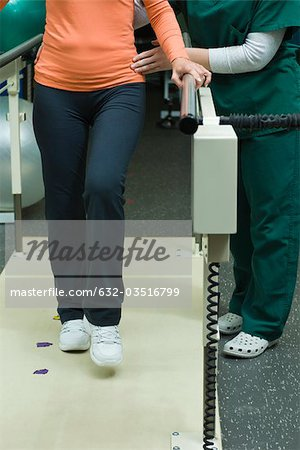 Patient learning to walk and regain leg coordination with assistance from physical therapist Stock Photo - Premium Royalty-Free, Image code: 632-03516799