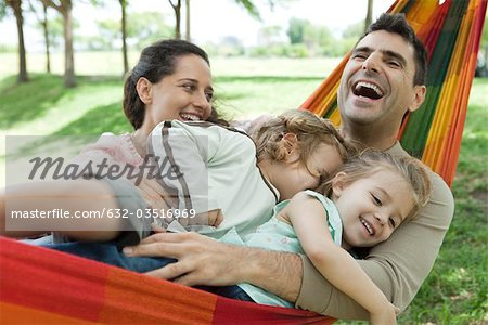 Family laughing together on hammock