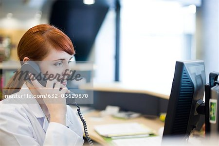 Female receptionist talking on phone Stock Photo - Premium Royalty-Free, Image code: 632-03629870