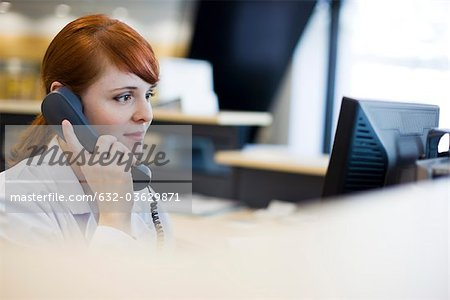 Female receptionist talking on phone Stock Photo - Premium Royalty-Free, Image code: 632-03629871