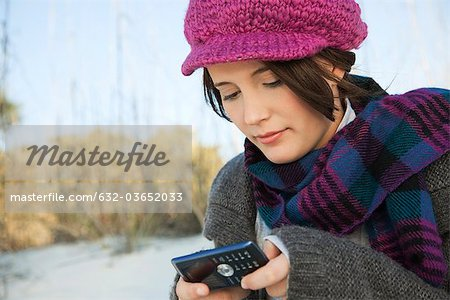 Teen girl text messaging at the beach Stock Photo - Premium Royalty-Free, Image code: 632-03652033