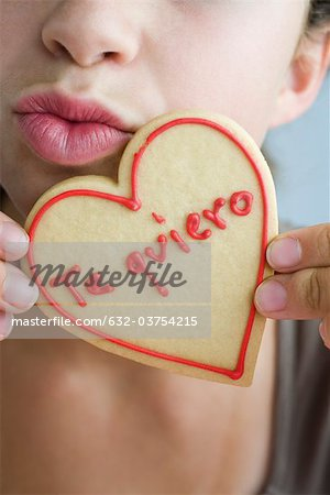 Woman puckering lips, holding heart-shaped cookie Stock Photo - Premium Royalty-Free, Image code: 632-03754215