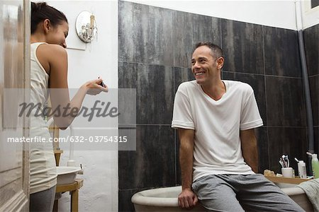 Couple talking and laughing in bathroom Stock Photo - Premium Royalty-Free, Image code: 632-03754315