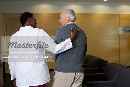Doctor walking and talking with patient Stock Photo - Premium Royalty-Free, Image code: 632-03754417