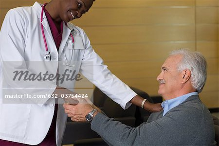 Doctor reassuring patient in waiting room Stock Photo - Premium Royalty-Free, Image code: 632-03754424
